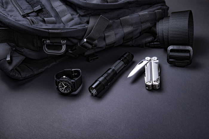 Everyday carry (EDC) items for men in black color - backpack, tactical belt, flashlight, watch and silver multi tool. Survival set. Minimal concept.